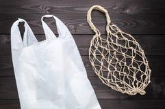 Hemp string bag versus plastic bag on dark background stock photo