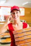 Hemsändning - boxas hållande pizza för kvinnan Arkivfoton
