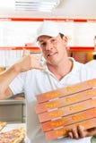 Hemsändning - boxas hållande pizza för manen Arkivbild