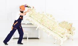 Hemsändningbegrepp Kuriren levererar möblemang i fall att av flyttar sig ut, förflyttning Laddaren flyttar soffan, soffa 308 mäss arkivbild