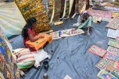 Hemslöjder är perpared till salu av den lantliga indiska mannen och kvinnan i den Pingla byn, Indien Arkivbild