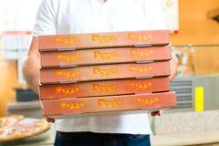 Hemsändning - boxas hållande pizza för manen Arkivfoto