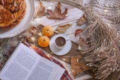 Hemtrevlig dag för nedgång med boken och kaffe arkivfoton