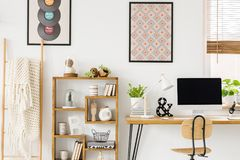 Hemtrevlig filt på en stege, en träbokhylla med garneringar och royaltyfri fotografi