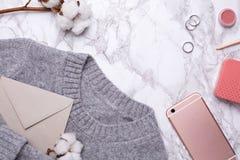 Hemtrevlig grå tröja med mobiltelefonen och bomullsblomman på en marmorbakgrund royaltyfri bild