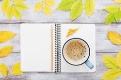 Hemtrevlig höstfrukost med morgonkoppen kaffe och den öppna anteckningsboken på lantlig träbästa sikt för tabell Lekmanna- lägenh Arkivbild