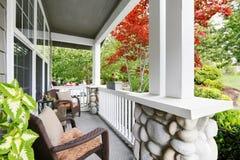 Hemtrevlig ingångsfarstubro med vita kolonner och vide- stolar Royaltyfri Bild