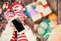 Hemtrevlig jul hemma Kvinnlign räcker den hållande mobiltelefonen Fot för kvinna` s i julstrumpor, stor gåva på bokehljusbackgro arkivfoton