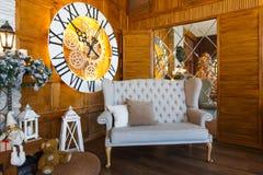 Hemtrevlig jul som är inre med klockan och den mjuka soffan Arkivfoton