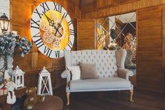 Hemtrevlig jul som är inre med klockan och den mjuka soffan Royaltyfri Foto