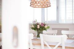 Hemtrevlig matsal som är inre med blommagarnering i ett vitt rum av en modern husnärbild royaltyfria bilder