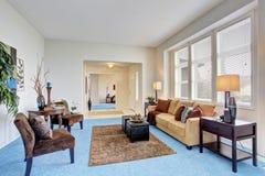 Hemtrevlig modern vardagsrum med det blåa mattgolvet arkivfoton
