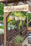 Hemtrevlig och inviterande trädgård med många växter och välkommet tecken royaltyfria foton