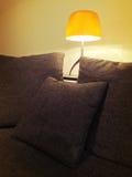 Hemtrevlig orange lampa och bekväm soffa Arkivfoton