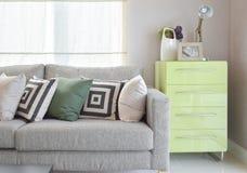 Hemtrevlig soffa med geometriska modellkuddar och den gröna serveringsbordet Royaltyfri Fotografi