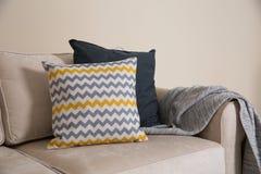 Hemtrevlig soffa med kuddar och pl?det Id? f?r vardagsruminredesign arkivfoto