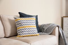 Hemtrevlig soffa med kuddar och pl?det n?ra den ljusa v?ggen Id? f?r vardagsrum arkivfoton