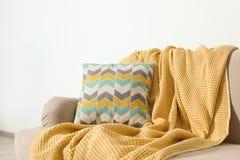 Hemtrevlig soffa med kudden och pl?det Id? f?r vardagsruminredesign royaltyfria bilder