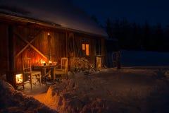 Hemtrevlig trästuga i mörk vinterskog Royaltyfri Fotografi