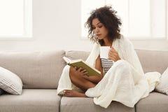 hemtrevlig utgångspunkt Ung fundersam kvinna med boken arkivfoto