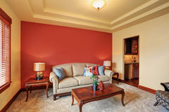 Hemtrevlig vardagsrum med den antika beigea soffan och den röda väggen bakom Fotografering för Bildbyråer