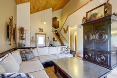 Hemtrevlig vardagsrum med det höga trävälvde tak- och mattgolvet Royaltyfri Fotografi
