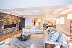 Hemtrevlig vardagsrum med en stenvägg royaltyfri foto