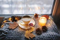 Hemtrevlig vinter- eller höstmorgon hemma Varmt kaffe med den guld- metalliska skeden, värme filt-, girland- och stearinljusljus royaltyfri bild