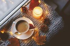 Hemtrevlig vinter- eller höstmorgon hemma Varmt kaffe med den guld- metalliska skeden, värme filt-, girland- och stearinljusljus royaltyfria foton