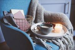 Hemtrevlig vinterhelg hemma Morgon med kaffe eller kakao, böcker, varm stucken filt och nordisk stilstol Hygge begrepp