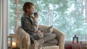 Hemtrevlig vinterlivsstil Ung lycklig kvinna som dricker koppen kaffe som bär det stack tröjasammanträdehemmet vid det stora föns stock video