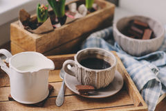 Hemtrevlig vintermorgon hemma Kaffe mjölkar och choklad på trämagasinet Huacinth blommar på bakgrund Varmt lynne Arkivbilder