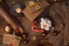 Hemtrevlig vintersammansättning med en kopp, stearinljus, en traditionell julsötma, en girland och en tröja på tappningen träfest royaltyfri fotografi