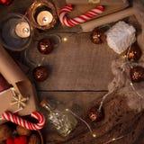 Hemtrevlig vintersammansättning med stearinljus, traditionell julsötma, girlanden och tröjan på tappningen träfestlig bakgrund arkivbilder