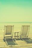 Hemtrevlig vit belägen mitt emot seascape för strandstol med tappning filtrerade bild Royaltyfria Bilder