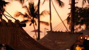 Hemtrevlig vit hängmatta på stranden mot en bakgrund av simbassängen, havet och solnedgången