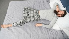 Hemtrevliga dr?mmar sovande och vaket energi och tr?tthet sk?ggig manhipsters?mn i morgon brutal s?mnig man i sovrum royaltyfri bild