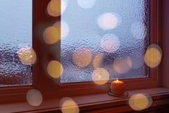 Hemtrevliga frostade fönster-, stearinljus- och bokehljus Royaltyfri Foto