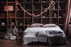 Hemtrevlighet-, komfort-, inre- och feriebegrepp - det hemtrevliga sovrummet med säng och girlanden tänder hemma En kugge med böc arkivbild