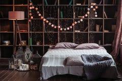 Hemtrevlighet-, komfort-, inre- och feriebegrepp - det hemtrevliga sovrummet med säng och girlanden tänder hemma En kugge med böc royaltyfria bilder