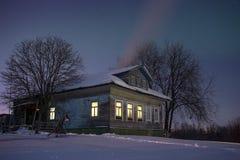 Hemtrevligt gammalt ryssbyhus i den bittra förkylningen Vinternattlandskapet med snö, stjärnor, rök från pannan och värme Arkivbilder