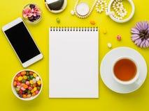 Hemtrevligt hörn för en flicka med en anteckningsbok, smartphone, blommor, jew arkivfoto