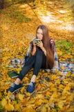 Hemtrevligt höstmodellfoto i gula sidor Flickasammanträde i höstskogen, i pläd och drinkcofee Arkivbilder