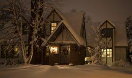 Hemtrevligt hus i snö på natten Royaltyfri Bild