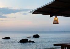Hemtrevligt kafé med bambulampor på stranden på den härliga solnedgången Royaltyfri Foto