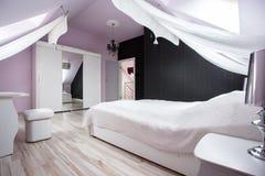 Hemtrevligt och vitt sovrum Arkivbild