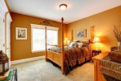 Hemtrevligt sovrum med sniden wood säng och höga poler Arkivfoto