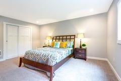 Hemtrevligt sovrum med träsäng och som bygger i garderob arkivbild