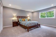 Hemtrevligt sovrum med träsäng och som bygger i garderob fotografering för bildbyråer