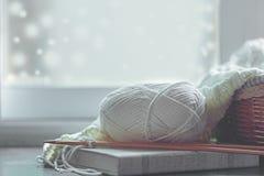 Hemtrevligt vinterhem med varmt stuckit tröjor och garnnystan nära fönsterbrädan, hem- hobbyer, tappningsignal royaltyfria bilder